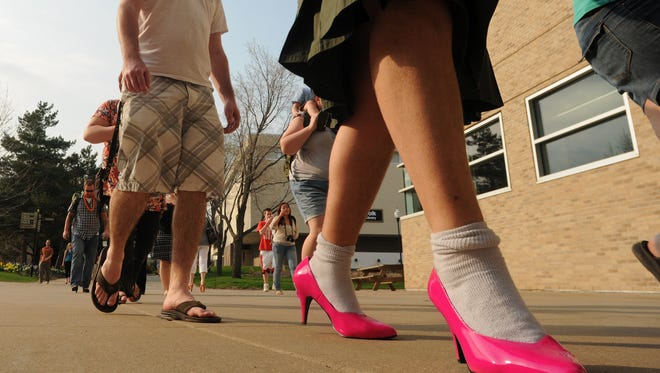 UW-Oshkosh student Nick Brewer wears a pair of hot pink patent leather high heels at the Walk a Mile in Her Shoes event  in this file photo. This year's event is Wednesday, May 4.