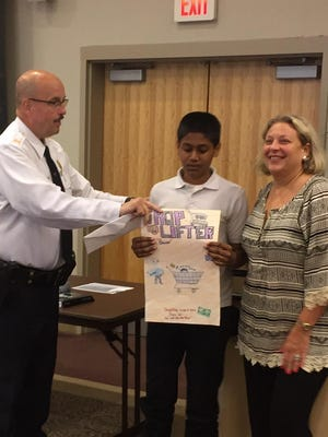 Vraj Patel, a Wallace Intermediate School seventh-grader, is congratulated by Vineland Police Captain Tom Ulrich and Vineland School Superintendent Mary Gruccio for his third-place finish in a poster contest.