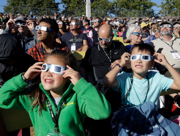 A crowd wears protective glasses as they watch the