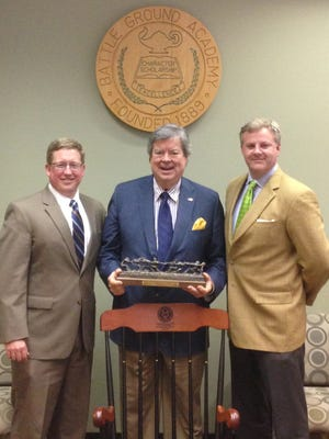BGA Head of School Will Kesler (left) and incoming Board Chair Tyler Berry (right) present outgoing Chair Eddie Lunn with a statue portraying BGA's annual tug-of-war for his service.