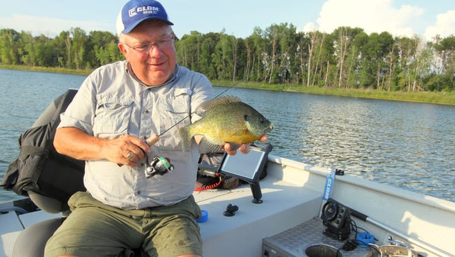 """Dave Genz grins at a plump bluegill pulled up on a short rod on his """"holey boat"""" earlier this summer. In pioneering many of today's most effective ice fishing concepts, Dave turned the process on its head and brought ice fishing to summer angling by installing special holes (lower right) through which to fish in his boat."""
