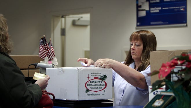 A U.S. Postal Service employee handles a package at the Collins Road location in Lansing. The postal service says it's reactivating a plan to shift the Collins Road operations to Grand Rapids.
