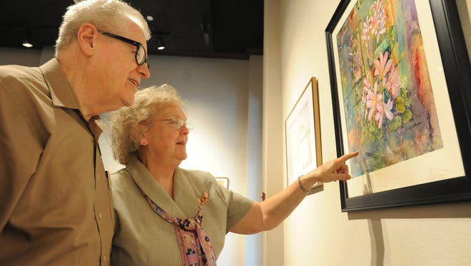 First-place winner in the graphics division, William Wood, and Myrna Wood look at the art during the opening reception for the Shreveport Art Club's juried exhibit held at the Louisiana State Exhibit Museum Sunday.