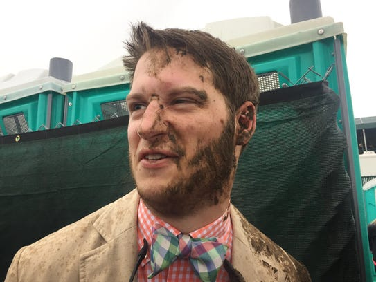 A man with mud smeared on his face in the infield.