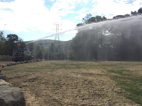 A water truck sprays the now empty portion of the park