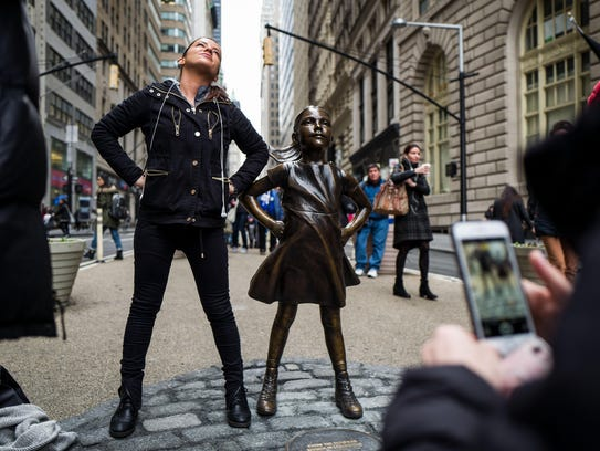 A woman poses for a photo with 'The Fearless Girl'