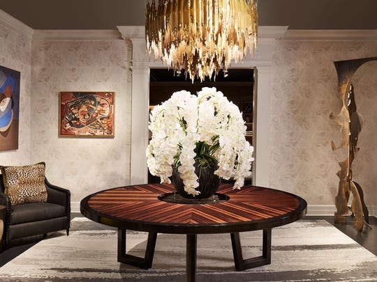 A huge brutalist brass chandelier hovers over an exotic wood table and equally large vase of orchids.