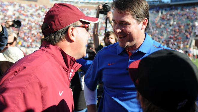 Florida Gators head coach Will Muschamp meets with Florida State Seminoles head coach Jimbo Fisher before the game at Doak Campbell Stadium.