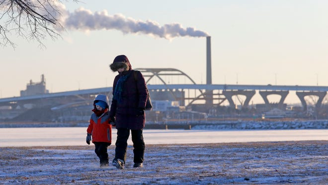 Amanda Timm and her 3-year-old son, Isaiah, are bundled up as they walk through Veterans Park in Milwaukee on Monday, Jan. 1, 2018. High temperatures will struggle to reach the low teens this week, though many spots in southern Wisconsin will likely see high temperatures only in the single digits with lows of 5 above tominus 10.