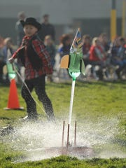 A third grader releases a water rocket during a rocket
