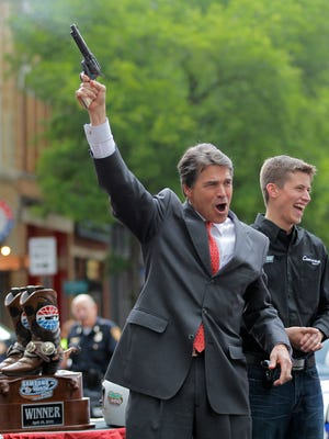 In this April 15, 2010 file photo, Texas Republican Gov. Rick Perry fires a six shooter filled with blanks as NASCAR driver Colin Braun looks on at an event in downtown Fort Worth, Texas. Texas is preparing to give college students and professors the right to carry guns into their classrooms, adding momentum to a national campaign to open up another prominent part of society to firearms.
