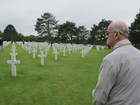 "Ralph Ticcioni takes off his cap in respect for the dead at the American Cemetery in Normandy, France. Ticcioni, who was attached to the 82nd Airborne, was moved by seeing more than 9,000 graves of Americans killed in Europe during World War II. Of protesters' use of Nazi flags, Ticcioni of New Berlin says: ""It's a slap in the face for all the guys buried over there. I thought we did it once, got rid of (fascism) but it's popping up again."""