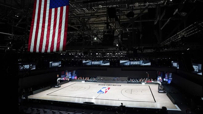 The court sits empty after a postponed NBA basketball playoff game between the Milwaukee Bucks and the Orlando Magic, Wednesday in Lake Buena Vista, Fla.