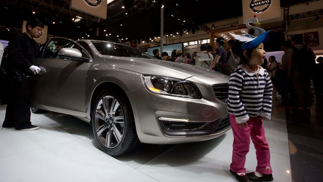 A child poses for photos near a Volvo S60L at the China Auto in Beijing in April