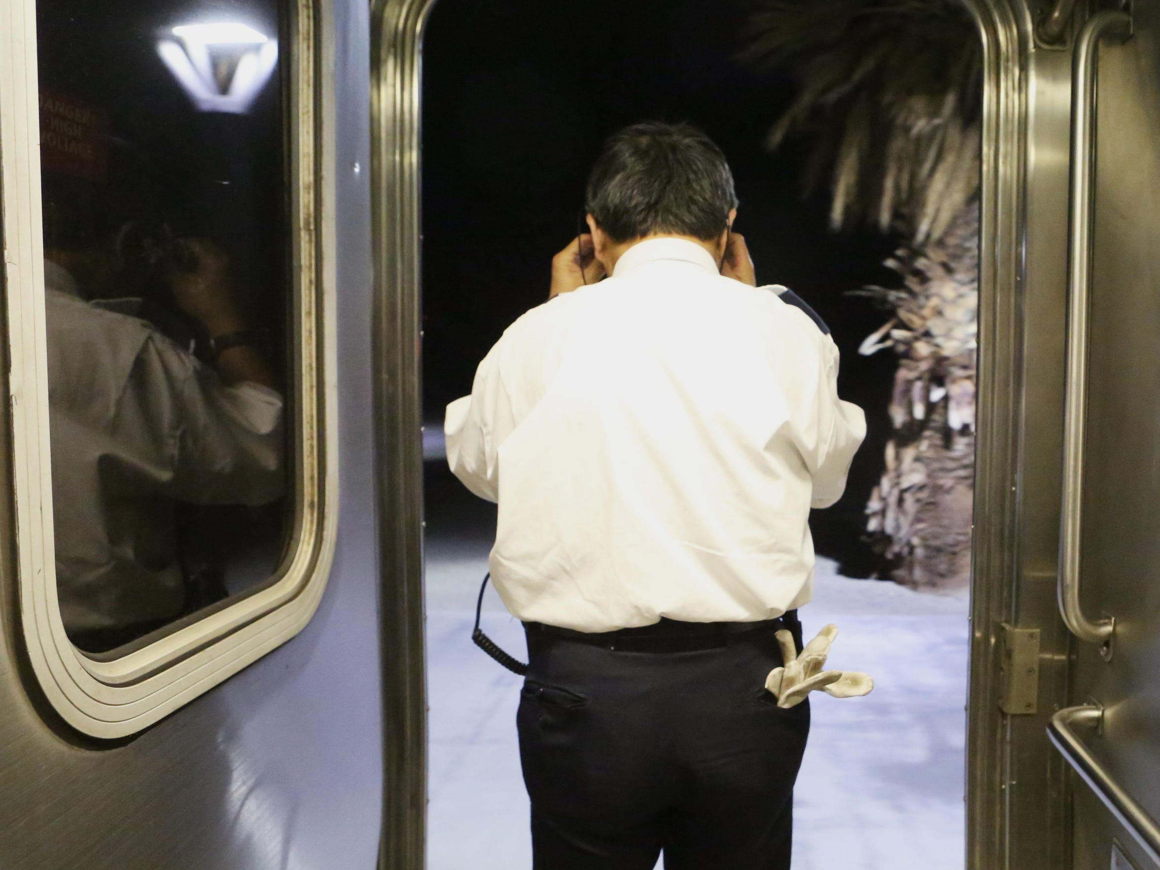A train attendee adjusts his glasses as the Amtrak