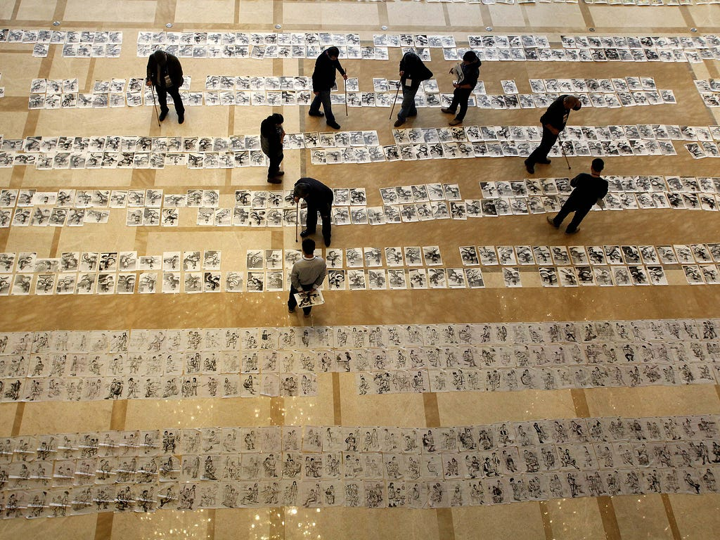 Officials inspect student exam papers during the Jan. 12 national college entrance test to qualify for entry to the higher academy of fine arts in Xi'an, China.