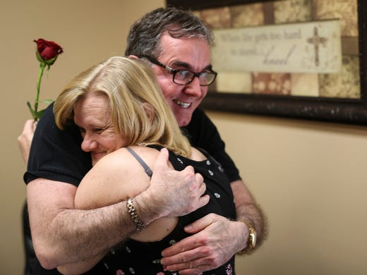 Dr. Barry Hardison, right, receives a hug from a patient