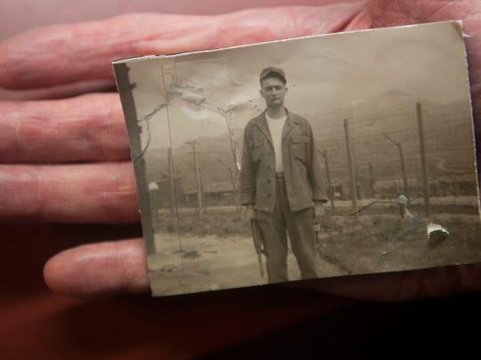 Korean War veteran Stan Levin of Maple Shade holds a 1953 photograph of himself in Korea.