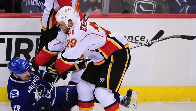 Calgary Flames defenseman Deryk Engelland (29) checks Vancouver Canucks forward Henrik Sedin (33) during the second period in game one of the first round of the the 2015 Stanley Cup Playoffs at Rogers Arena.