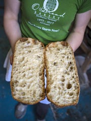 Sophie Conway shows a ciabatta loaf cut in half at O Bread Bakery at Shelburne Farms in Shelburne on Friday, April 22, 2016.