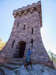 Artist Katharine Montstream checks out the Ethan AllanTower in Burlington on Friday, October 20, 2017, looking for a place to put one of her paintings.  To commemorate thirty years of work, Montstream is leaving one painting a day for people to find in a different location for thirty days. Sunday there will be a painting to be found somewhere in the park.