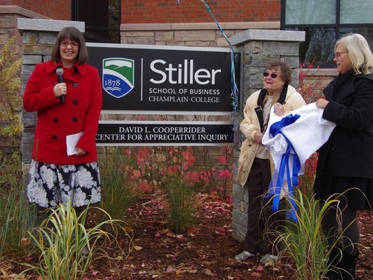 Lindsey Goodwin, left, associate professor of management at the Robert P. Stiller School of Business, and David Cooperrider's mother, Fran and his wife, Nancy, unveiled the sign marking the official opening of the David L. Cooperrider Center for Appreciative Inquiry at Champlain College.