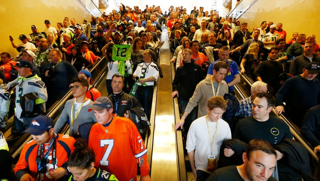 Football fans make their way to trains in Secaucus, N.J. Many fans complained of long delays and hot trains.