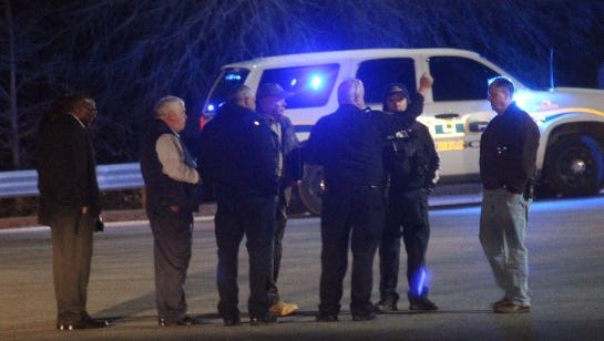 Anderson County Coroner Greg Shore, second from left, and Anderson Police Chief Jim Stewart, far right, consult with investigators at the scene of a fatal shooting behind Sam's Club on Monday night.