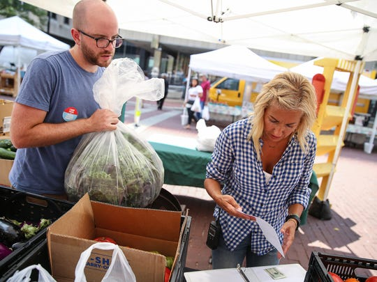 "From left, City Market's Joe Perin and Stevi Stoesz weigh fresh produce donations to be hauled off to Wheeler Mission's men's shelter, Indianapolis, Wednesday, July 19, 2017. The Original Farmer's Market at City Market downtown encourages customers to purchase an item to contribute to the weekly collection in a program called ""Buy 2, Give 1."" Vendors participate as well and the produce donations are taken by BlueIndy to a local shelter or food pantry after the market every Wednesday."