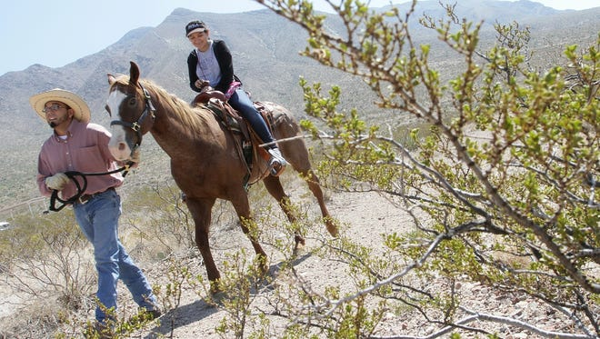 Ashley Shamaley is led on a horseback ride by Alex Berroteran of the Serna Ranch during the Eighth Annual Chihuahuan Desert Fiesta at Franklin Mountains State Park.