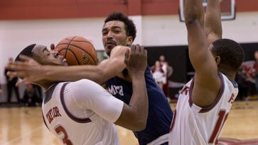 Monmouth's  Micah Seaborn tries driving between Rider's Jimmie Taylor and Kealen Ives during first half action. Monmouth Men's Basketball vs Rider University in Lawrenceville, NJ on February 12, 2016.