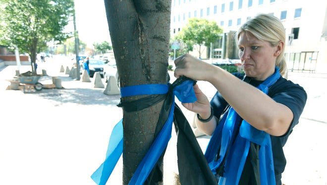 Court deputy for the Monroe County Sheriff Shelly Haefner places black and blue ribbons on Exchange Boulevard, in preparation for the funeral service of officer Daryl R. Pierson in Rochester.
