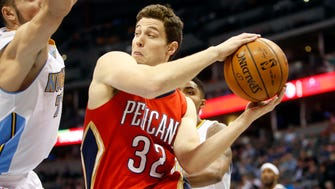 New Orleans Pelicans guard Jimmer Fredette (32) looks to pass the ball past Denver Nuggets forward Joffrey Lauvergne (77) during the first half at Pepsi Center.