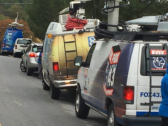 Television news trucks line the streets of Caitlyn