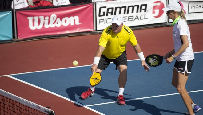 Mike Gates reaches low to return a shallow hit during the mixed doubles 50 and over championship match as his partner, Chris Anderson, looks on during the US Open Pickleball Championships at East Naples Community Park Thursday, April 28, 2016.