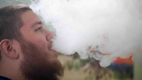 Adam Arrington, of Dover, uses an electronic cigarette. The battery-powered devices produce an odorless vapor that typically contains nicotine and flavorings. Delaware lawmakers in the House of Representatives passed legislation Thursday banning the devices indoors, except for vape shops.