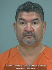 Martin Benavidez, 51, of San Tan Valley, was arrested after a neighbor saw his puppy hanging from his hind legs, the Pinal County Sheriff's Office said.