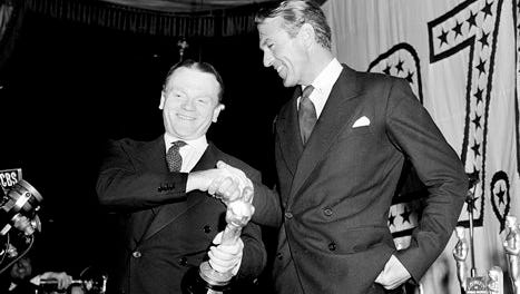 """In this March 4, 1943, file photo, actor Jimmy Cagney, left, is congratulated by Gary Cooper after receiving the best actor Oscar statuette for his role in """"Yankee Doodle Dandy"""" at the 1942 Academy Awards banquet at Cocoanut Grove, Ambassador Hotel, in Los Angeles. The auctioneer Nate D. Sanders will sell Cagney's Oscar statuette to the highest bidder Thursday."""