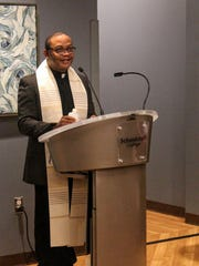 The Rev. Luke Iwuji says a blessing at the St. Joe's Urgent Care clinic Thursday morning at Schoolcraft College.