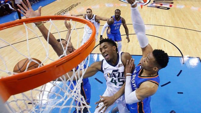 Utah Jazz guard Donovan Mitchell (45) shoots between Oklahoma City Thunder guard Josh Huestis, left, and guard Russell Westbrook, right, during the first half of Game 5 of an NBA basketball first-round playoff series in Oklahoma City, Wednesday, April 25, 2018.