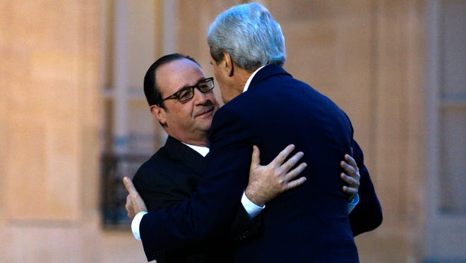 Secretary of State John Kerry, right, is embraced by French President Francois Hollande upon arrival at Elysee Palace in Paris on Jan. 16, 2015.