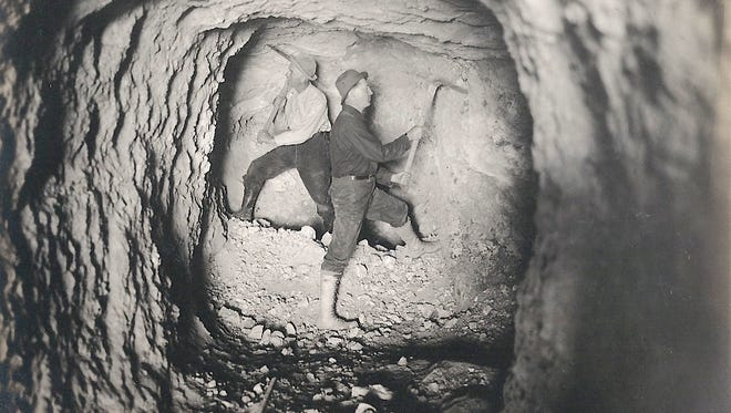 Two unidentified men at work in mine.