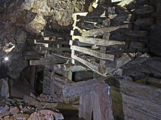 In this Aug. 14, 2018, photo, Jeremy MacLee looks at a timbers in a mine near Eureka, Utah.