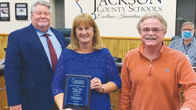 Superintendent Blaine Hess (left) and Board of Education Vice-President Jim Frazier (right) recognized Cathy Pitts (center) who retired as paraprofessional and aide at Ripley Elementary after 18 years of service.