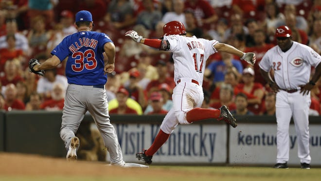 Cincinnati Reds second baseman Kris Negron (17) is out at first as the Chicago Cubs relief pitcher Carlos Villanueva (33) tags the base during their game at Great American Ball Park.