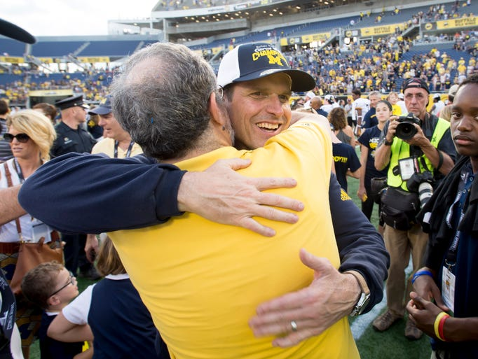 Michigan head coach Jim Harbaugh, right, gets a hug