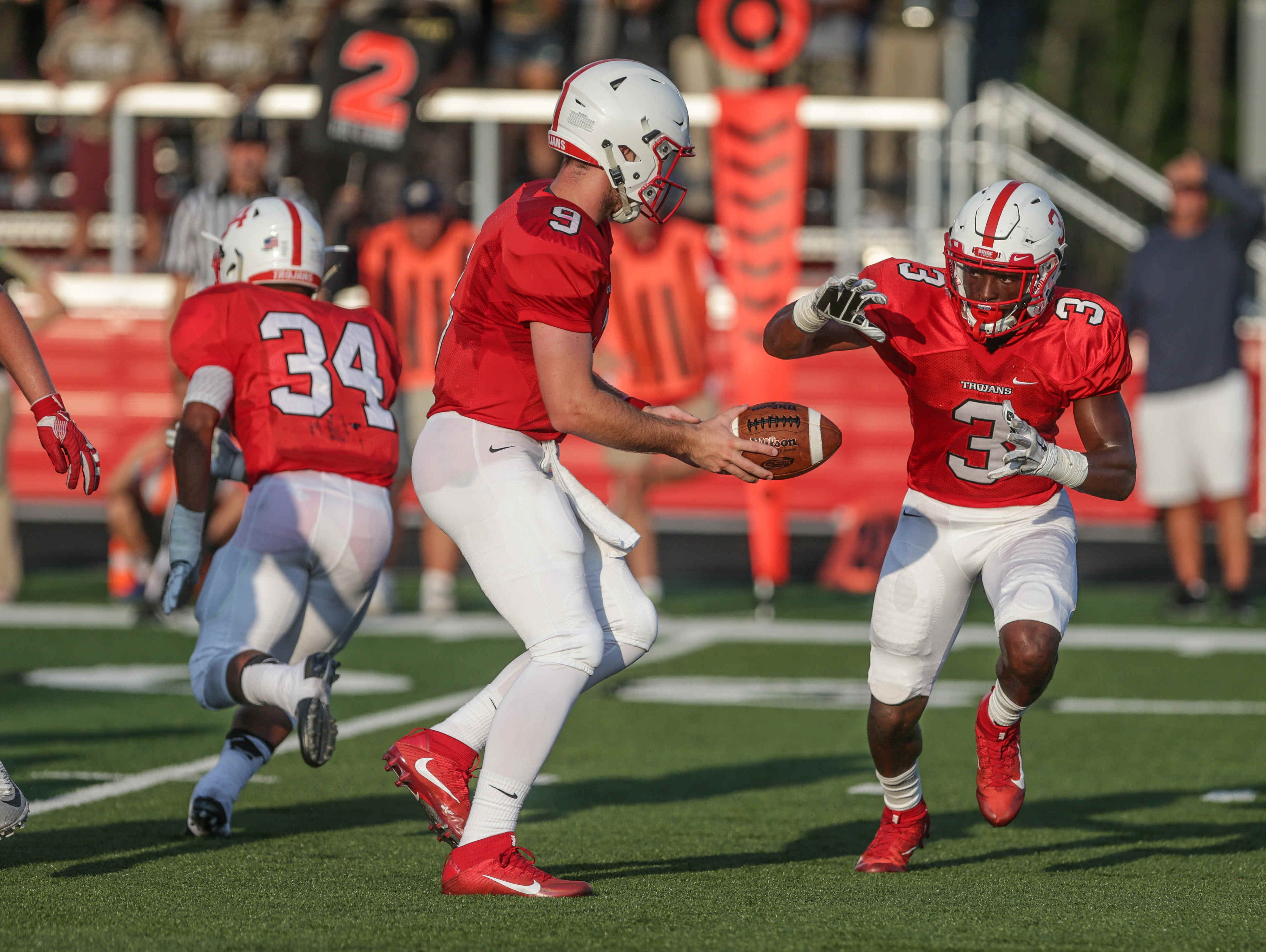 Center Grove's QB, #9, Jack Kellams hands the ball off to RB, #3, Russ Yeast, during the first game of the season, as Warren Central High School takes on Center GroveGrove High School at Center Grove, Friday August 19th, 2016.
