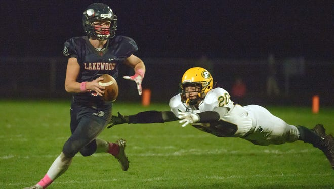 Pennfield defensive end Sam Nichols (20) dives to attempt a tackle on Lakewood quarterback Parker Smith.