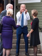 Vice President Joe Biden, center, shows some some loose change he picked up outside the Penny Cluse Cafe in Burlington before participating in a Cancer Moonshot Roundtable at the University of Vermont on Friday, October 21, 2016. With Biden are U.S. Senator Patrick Leahy and Marcelle Leahy, left, and Democratic gubernatorial candidate Sue Minter.
