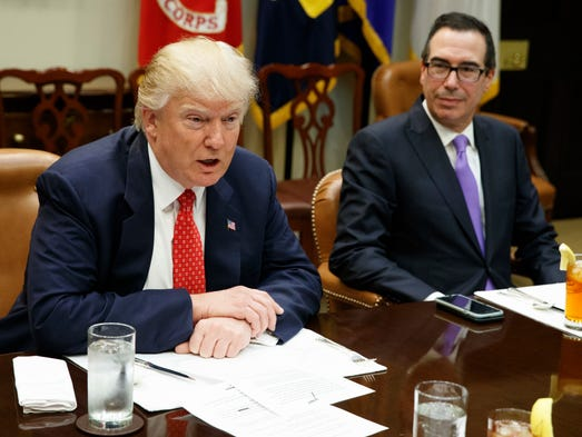 Treasury Secretary Steven Mnuchin listens at right